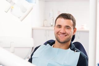 man sitting in dental exam chair smiling brightly I oral surgery in harleysville pa